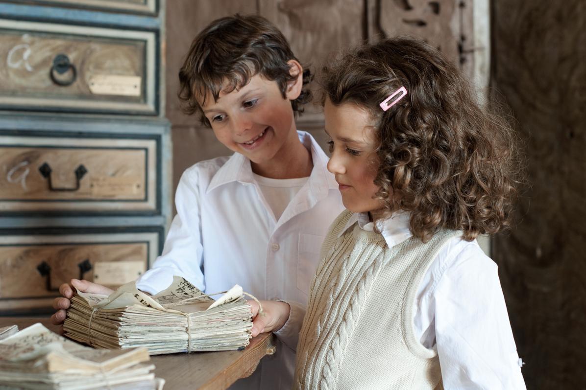 Kinder mit Dokumenten im Archivraum, Schloss Weikersheim; Foto: Staatliche Schlösser und Gärten Baden-Württemberg, Niels Schubert