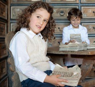 Kinder mit historischen Dokumenten in Schloss Weikersheim; Foto: Staatliche Schlösser und Gärten Baden-Württemberg, Niels Schubert