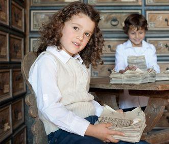 Kinder mit Papierstapeln im Archivraum, Schloss Weikersheim; Foto: Staatliche Schlösser und Gärten Baden-Württemberg, Niels Schubert